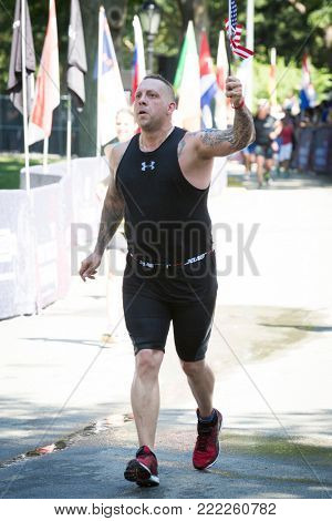 NEW YORK - JUL 16 2017: Athlete holding the American Flag crosses the finish line in Central Park of the Panasonic New York City Triathlon Race, the only International Distance triathlon in NYC.