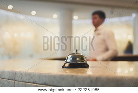 Hotel accommodation call bell on reception desk, contemporary interior, blurred man guest on background, copy space