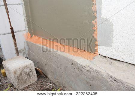 Unfinished house foundation plastering wall with fiberglass mesh, plaster mesh, rigid foam insulation.