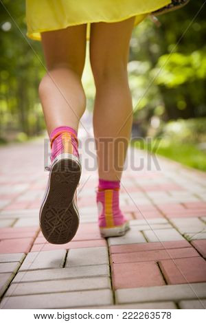 Closeup of girl's legs jumping on the paving tiles. Playing hopscotch on school yard on sunny day. Leisure activities outdoors.