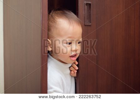 Cute little Asian 18 months / 1 year old toddler baby boy child wearing white sweater is hiding in the closet at home, Funny kid play hide and seek peeking / looking out of wooden open door wardrobe