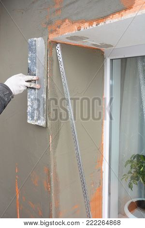 Contractor plastering wall with spatula, fiberglass mesh, plaster mesh after  foam rigid insulation. Window sill area insulation with stucco wall.
