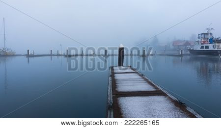An empty boat dock on a cold, misty morning