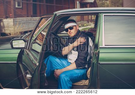 guy in the nineties sits behind the wheel of a car wearing sunglasses