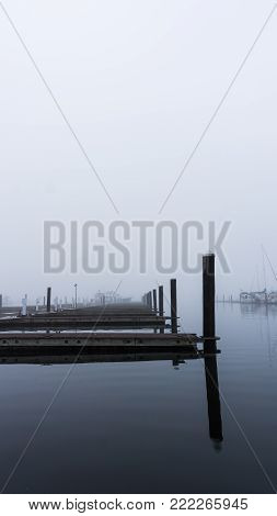 Diminishing view of docks on a misty morning - portrait view