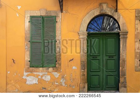 old green door and window of ancient european yellow building, Cyprus