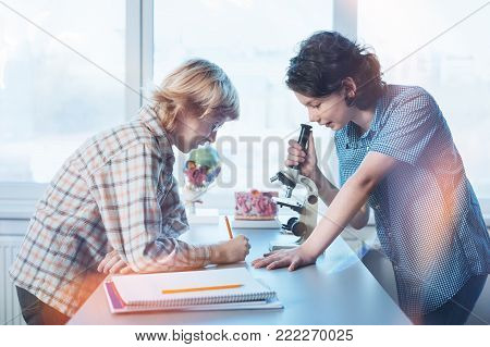 Noting the details. Intelligent attentive inspired boy telling his friend what he observing through the microspore while fulfilling practical assignment in biology class