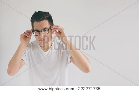 Close up portrait of a funny man with eyeglasses. Weird young guy has eyesight problems. The concept is isolated on a white background