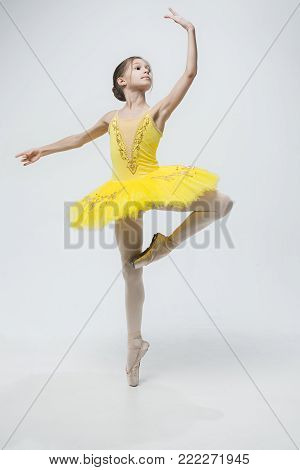 Young classical dancer on gray studio background. Ballerina project.