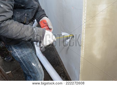 Contractor install rain gutter drain downspout pipe holder with measure tape. Guttering