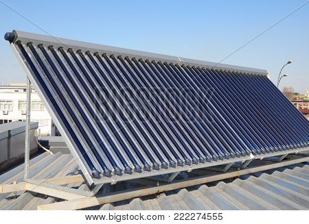 Modern House Roof with Solar Water Heater, Solar Panels as energy efficiency solution. Vacuum solar water heating system.