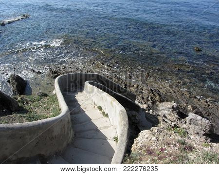 Concrete staircase down to the sea . Spiral stairs descent to the water . Tuscany, Italy