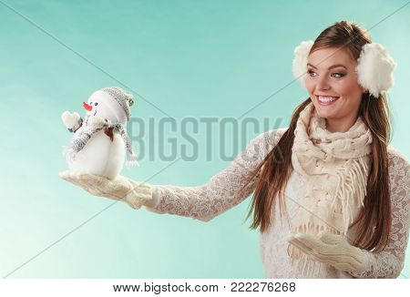 Smiling pretty cute woman holding little snowman. Attractive girl in earmuffs and white sweater pullover in studio on green. Winter fashion. poster