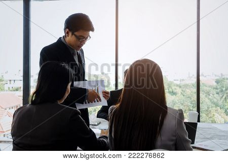 asian project manager showing and presenting growth chart diagram of financial report or results of the year in meeting room at office, investment, company success, and teamwork concept, vintage tone