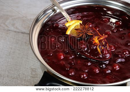 Freshly cooked cranberry sauce with orange peel and citrus slices in a saucepan