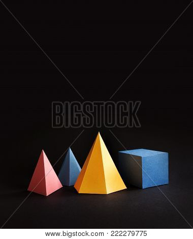 Colorful abstract geometric shape figures still life. Three-dimensional pyramid prism rectangular cube on black background. Yellow blue pink malachite colored objects, copy space.