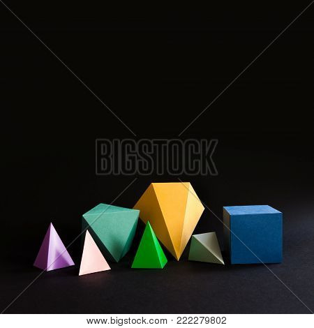 Colorful minimalistic composition abstract geometric solid figures on black background. Pyramid prism rectangular cube yellow blue pink green colored figures. Copy space.