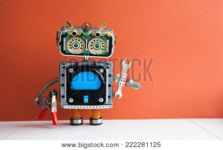 Service work maintenance concept. Robot handyman with hand wrench, pliers on red background. Copy space.