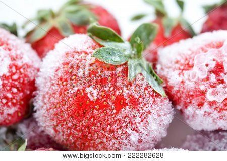 Frozen berries. sweet soft red strawberry fruits with a seed-studded surface. Macro view, detailed seeds, achene and ice. Soft focus.