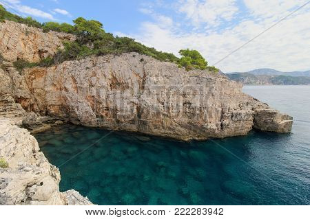 Scenic view of an empty sea cave, shallow water and steep and rugged cliff on the Lokrum Island in Croatia.