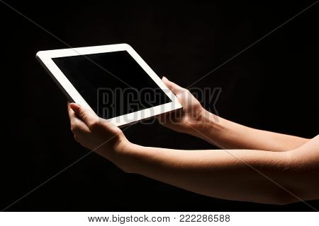 Female hands holding digital tablet with blank screen. Caucasian woman using device with emty screen, copy space for advertisement, isolated on black background