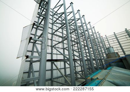 A high iron fence made of gray intertwining pipes on the roof.  in the fog.