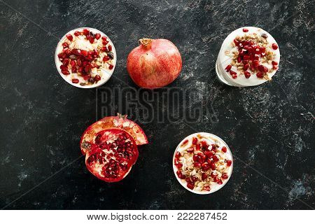 Over top view on healthy and delicious desset made from muesli, yoghurt and pomegranate on dark wooden background
