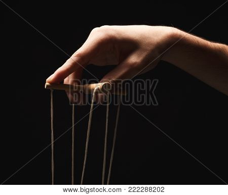 Male hand with marionette strings on black isolated backgorund. Manipulation, control and dictatorship concept, copy space