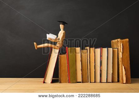 Educational background. Wooden marionette in graduation hat sitting on books and reading against empty classroom blackboard for copy space. Back to school concept