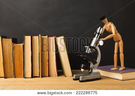 Educational background. Wooden marionette in graduation hat looking in microscope while standing near books, against empty classroom blackboard for copy space. Back to school concept