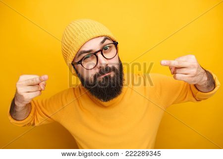 Handsome bearded man in yellow hat and t-shirt showing middle finger gesture.
