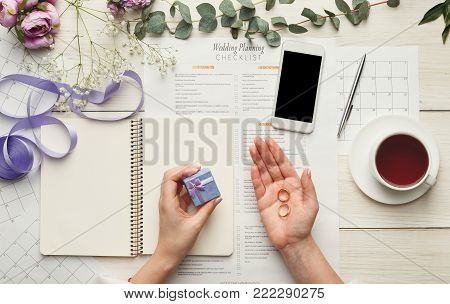 Wedding background with checklist and calendar. Female hands holding rings and arranging marriage, filling in planners on white wooden table with lots of tender bridal stuff, top view