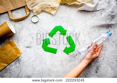 Eco-friendly life. Green paper recycling sign among waste paper, plastic, polyethylene on grey background top view.