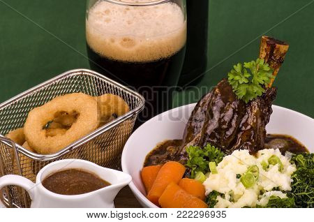 Lamb Shank Dinner. Traditional St Patrick's Day Lamb Shank served with Colcannon, Stout battered onion rings and a glass of Irish Stout.