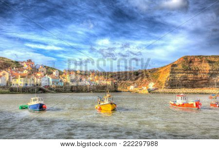 Staithes North Yorkshire England uk seaside town and holiday destination with boats in harbour in colourful hdr