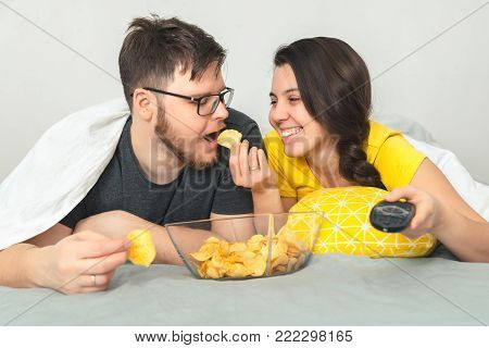 woman feed man with chips while wathcin interesting movie