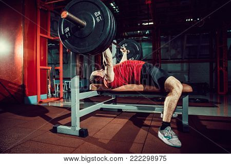 Very Strong man doing bench press workout in gym.