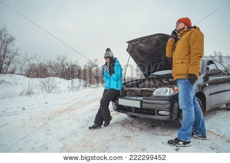 couple on the road with broken in cold winter day