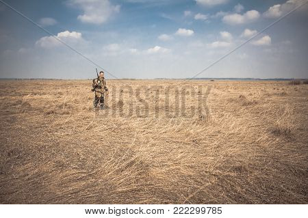 Hunter man with shotgun and hunting equipment standing in dry rural field with dry grass and blue sky during hunting season