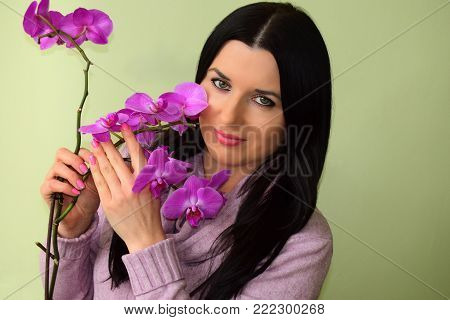The beautiful young woman the brunette with green eyes and a pink orchid. The woman is dressed in a pink dress, has pink lips and pink manicure