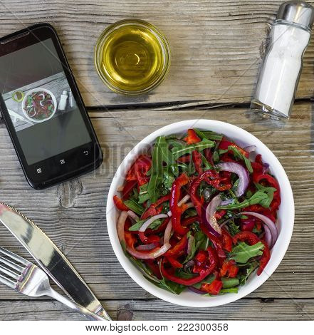 Vegetarian lunch. Salad of fresh vegetables, greens and red sweet peppers with olive oil. Concept: a healthy lifestyle.On the smartphone screen, a lunch display and a sticker with the inscription Invest in your health .