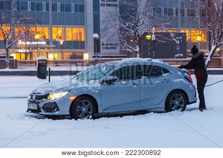 Woman Cleaning Her Car From The Snow.