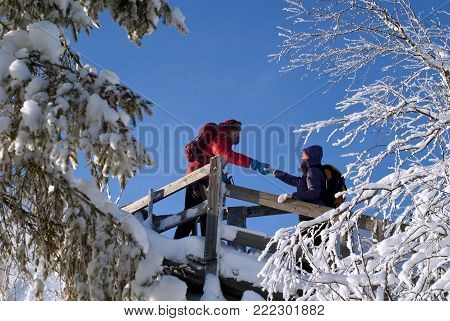 two people on an equipped trail in the winter mountains; the man holds out his hand to the woman, helping to climb up the slippery steps