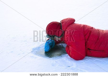 a man in winter lies on the surface of a frozen river and looks under the ice through the hole in snow