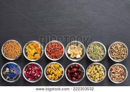 Selection of herbs on dark background with copy space - fenugreek, calendula, sandalwood, frankincense resin, horsetail, milk thistle, cornflower, rose petals, mullein, dried rose hips, chamomile, oak bark