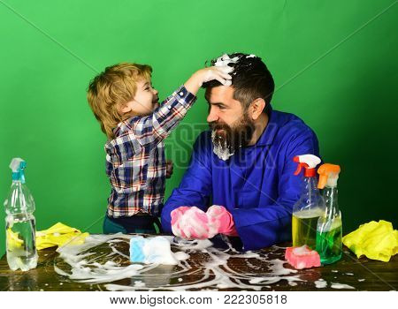 Son And Father Cleaning Together On Blue Background.