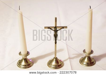 Cross And Candles On A White Tablecloth. Carol Singing, Cross And Candles On A White Table.
