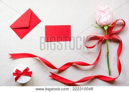 Flower and gift with a message card and letter - Birthday card with a cute gift box, a pink rose tied with red ribbon and bow, an envelope and a blank message card, on a vintage fabric background.