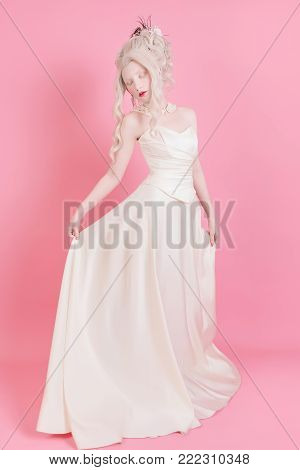 Woman princess with long white hair in white vintage wedding dress. Blonde princess girl with pale skin blue eyes and in the luxurious dress. Nice princess. Princess in wedding dress. Stylish princess