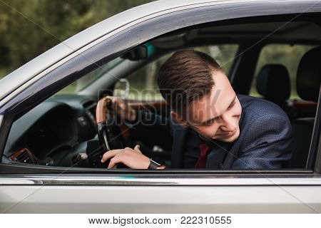 Successful businessman in a dark business suit with a red tie on the background of a gray car. Convenient transport. Modern safe transport. Business concept of a man on a background of transport